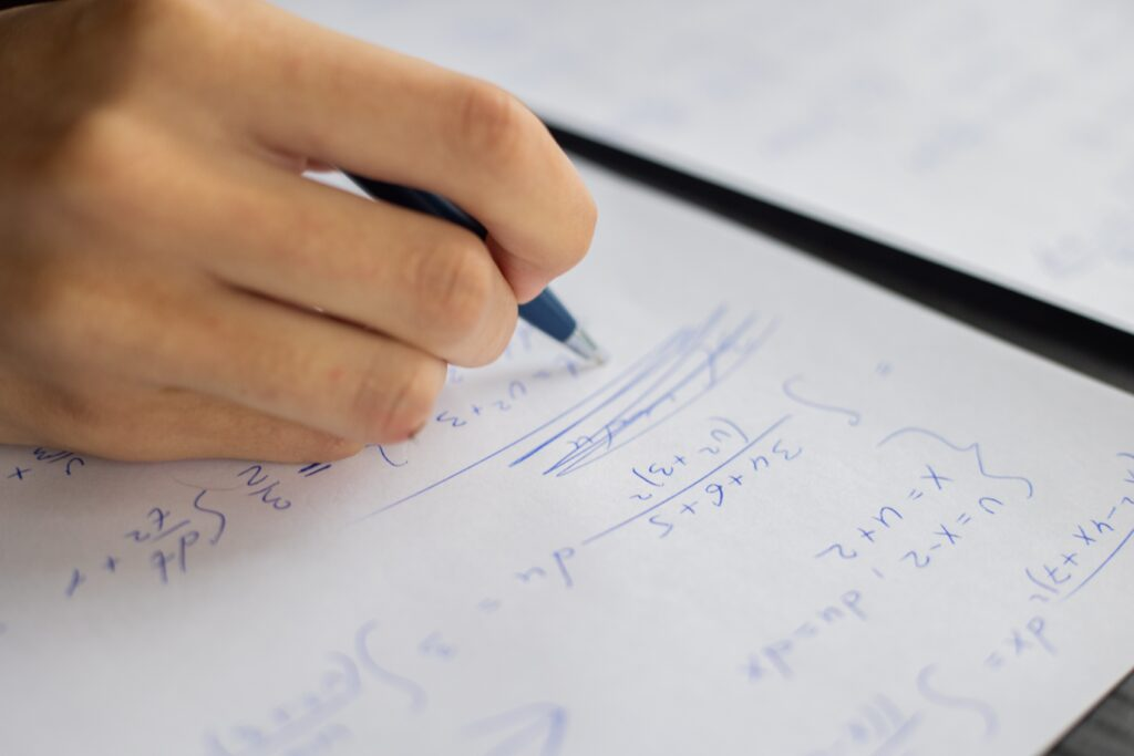 Student solving linear equations on a piece of paper with a pen